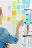 Rear view of a female artist looking at colorful sticky notes Stock Photos