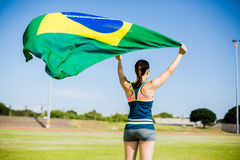 Rear view of female athlete holding an brazil flag. In the air Stock Photography