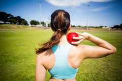 Rear view of female athlete preparing to throw shot put ball Stock Image