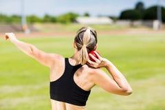 Rear view of female athlete preparing to throw shot put ball. In stadium royalty free stock image
