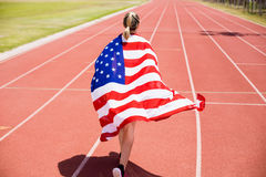 Rear view of female athlete running on the running track with american flag. In stadium Royalty Free Stock Image