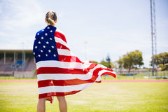 Rear view of female athlete wrapped in american flag. In stadium Stock Photos