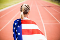 Rear view of female athlete wrapped in american flag. In stadium Stock Images