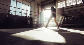 Female boxer training inside a boxing ring. Rear view of female boxer doing shadow boxing inside a boxing ring. Boxer practicing her punches at a boxing studio Royalty Free Stock Photography