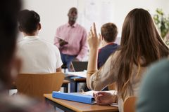 Rear View Of Female College Student Asking Question In Class Stock Photo