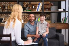 Rear view of female counselor writing in clipboard while father and son sitting on therapy. Session royalty free stock photos