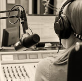 Rear view of female dj. Rear view of female dj working in front of a microphone on the radio royalty free stock image