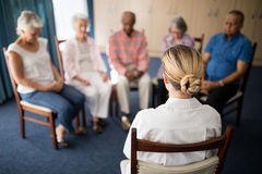 Rear view of female doctor meditating with senior people. At retirement home stock images