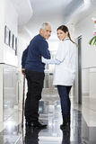 Rear View Of Female Doctor Walking With Senior Patient Stock Photos
