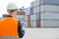 Rear view of female engineer using digital tablet in shipping yard Royalty Free Stock Photo
