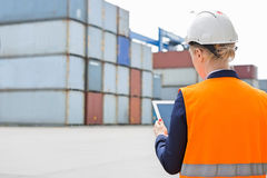Rear view of female engineer using digital tablet in shipping yard Royalty Free Stock Photography