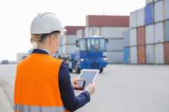 Rear view of female engineer using tablet PC in shipping yard Stock Photography
