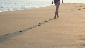 Rear view of female feet walking on golden sand at the beach with ocean waves at background. Legs of young woman. Stepping on sand. Barefoot girl at the sea stock footage