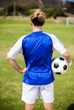 Rear view of female football player standing with a ball Royalty Free Stock Photography