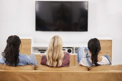 Rear View Of Female Friends Sitting On Sofa Watching Television Stock Image