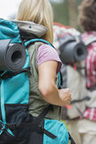 Rear view of female hiker carrying backpack with man in background outdoors Royalty Free Stock Image