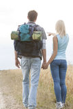 Rear view of female hiker showing something to man on field. Rear view of female hiker showing something to men on field Royalty Free Stock Photo