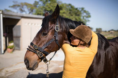 Rear view of female jockey embracing horse. While standing on field Royalty Free Stock Photo