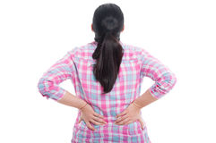 Rear view of a female with lower back pain. Holding hands to her spine on white background Royalty Free Stock Image