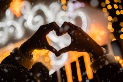 Rear view of female making heart shape with her hands in front o. F house decorated with Christmas lights. Love and holidays concept royalty free stock image