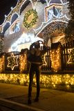 Rear view of female making heart shape with her hands in front o. Rear view of female who making heart shape in front of decorated house whit Christmas lights royalty free stock photography