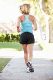 Rear View Of Female Runner Exercising On Suburban Street Royalty Free Stock Images