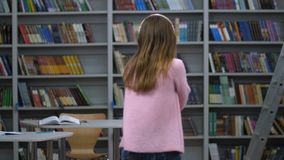 Young woman in headphones dancing back to camera. Rear view of female student in pink sweater and jeans dancing against bookshelves background. Blonde long