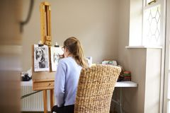 Rear View Of Female Teenage Artist Sitting At Easel Drawing Picture Of Dog From Photograph In Charcoal royalty free stock photography