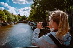 Rear view of female tourist taking photo of canal in Amsterdam on the mobile phone on sunny autumn day. Warm gold. Afternoon sunlight. Travel in Europe royalty free stock photo