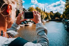 Rear view of female tourist taking photo of canal in Amsterdam on the mobile phone on sunny autumn day. Warm gold royalty free stock photos
