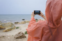 Rear view of female tourist taking photo of nature landscape with her mobile phone camera Stock Photography