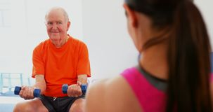 Rear view of female trainer training senior man in exercise at fitness studio 4k. Rear view of female trainer training senior man in exercise at fitness studio stock footage