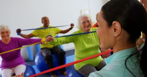 Rear view of female trainer training senior people in exercise at fitness studio 4k. Rear view of female trainer training senior people in exercise at fitness stock footage