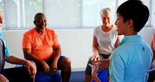 Rear view of female trainer training senior people in the fitness studio 4k stock footage