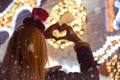 Rear view of female who making heart shape in front of decorated. House whit Christmas lights. Close up , snow, holidays and love concept stock image