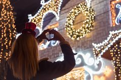 Rear view of female who making heart shape in front of decorated. House whit Christmas lights. Close up stock images