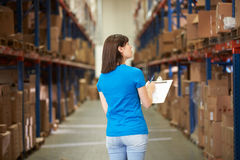 Rear View Of Female Worker In Distribution Warehouse. Looking at shelves stock image