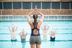 Rear view of female yoga instructor assisting senior swimmers. At poolside Royalty Free Stock Photo