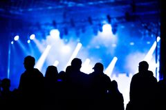Rear view of festival crowd during a concert. Bright stage lights in the background stock photography