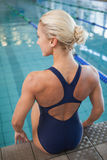 Rear view of a fit female swimmer sitting by pool Stock Photo