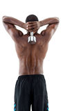 Rear view of a fit shirtless man lifting dumbbell Royalty Free Stock Image