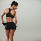 Rear view of a fit strong young woman Royalty Free Stock Images