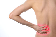 Rear view of a fit topless woman with back pain standing isolate Stock Photography