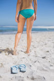 Rear view of fit woman in bikini on beach with flip flops on sand Stock Photography