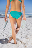 Rear view of fit woman in bikini on beach holding flip flops. On a sunny day Royalty Free Stock Photo