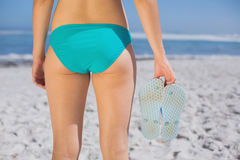 Rear view of fit woman in bikini on beach holding flip flops Royalty Free Stock Photography