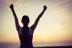 Rear view of fit woman cheering at promenade Royalty Free Stock Image