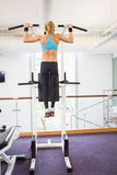 Rear view of fit woman doing pull ups at gym Stock Photography