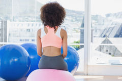 Rear view of a fit woman on fitness ball at gym Stock Images