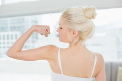 Rear view of fit woman flexing muscles in fitness studio Stock Images